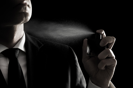 Elegante uomo in costume e cravatta usando colonia o profumo isolato su nero Archivio Fotografico