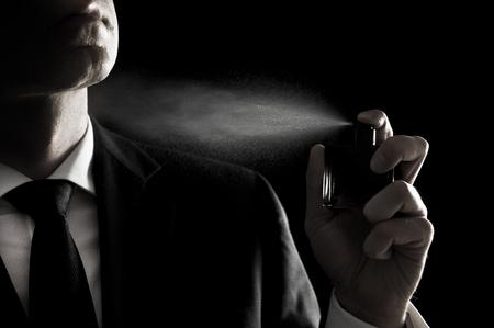 Homme élégant en costume et cravate en utilisant cologne ou parfum isolé sur fond noir Banque d'images