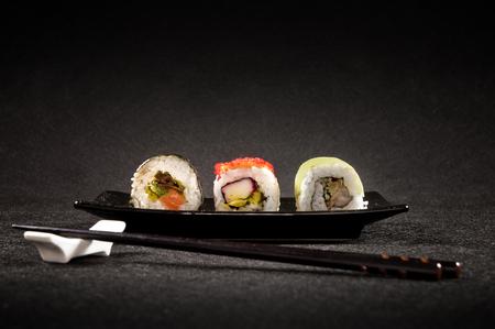 Luxurious sushi on black background - tasty japanese cuisine eaten with chopsticks Editorial