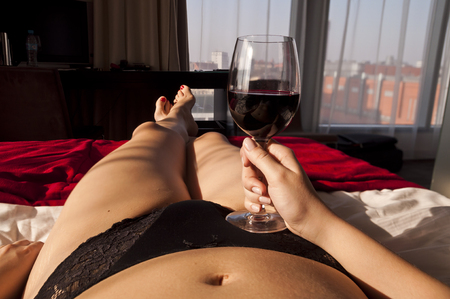 Sexy girl relaxing with a glass of wine lying in bed - point of view photo Stock Photo