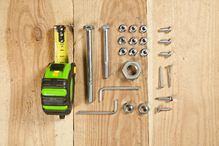Do it yourself - screws, nuts, tape measure, carpenter tools arranged orderly on wooden table. Top view. Stock Photo