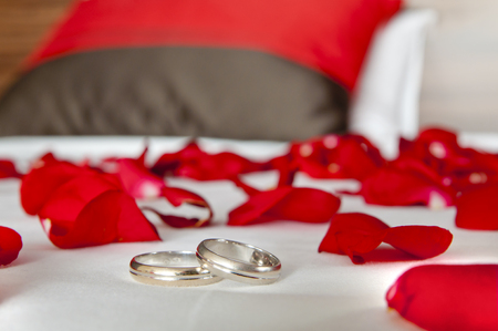 Wedding rings lying on a bed among rose petals