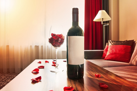 Bottle of wine on a table at sunset at home - romantic time in living room