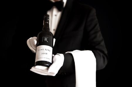 Waiter in tuxedo holding a bottel of red wine with custom etiquette Stock Photo