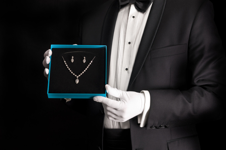 Elegant man in tuxedo presenting jewelery - isolated on black