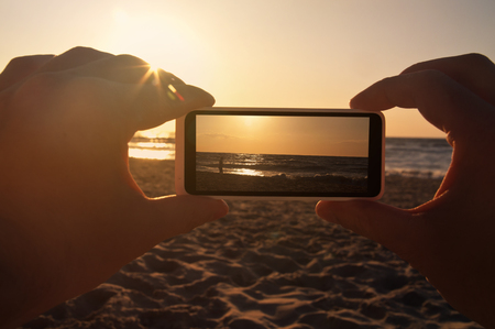 Man taking a photo of a sunset at sea with his phone - point of view shot
