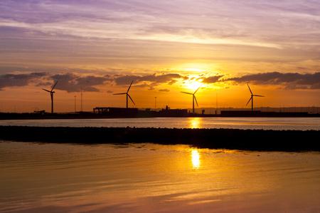 Wind turbines near seashore at sunset - ecology concept Stock Photo