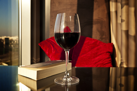 Glass of red wine and a book ready to enjoy in a cosy apartament