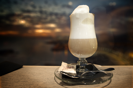 Cup of latte coffee in a panorama bar at sunset Stock Photo