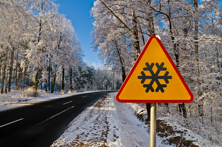 Road in wintertime - snowy forest on a sunny day. Warning sign.
