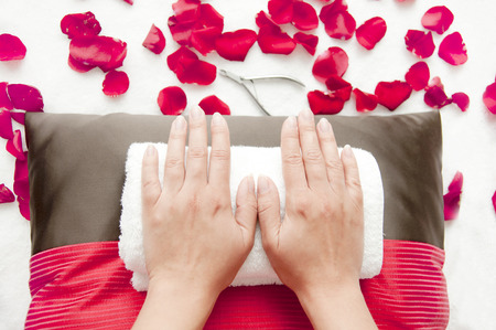 Manicure in a beauty salon - woman palms lying on pillow and towels ready for treatment