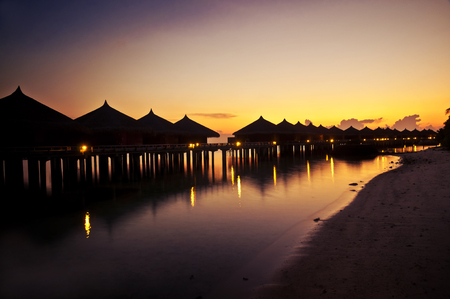 Sunset over a holiday resort - tropical huts along a beach at dusk