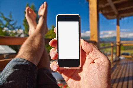 Man with smartphone in his hand relaxing on balcony - point of view photo Stock Photo