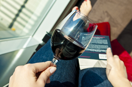 Point of view photo of a girl relaxing with wine and book Stock Photo