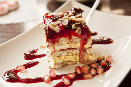 Tasty dessert on a plate - cake with cherry topping Stock Photo