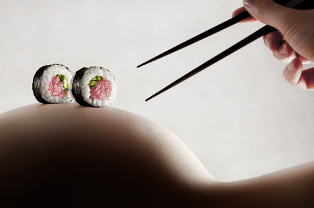 Eating sushi rolls with chopstics from a naked woman body