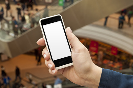 Smartphone with empty screen in woman hand in a shopping center - shopping application display Stock Photo