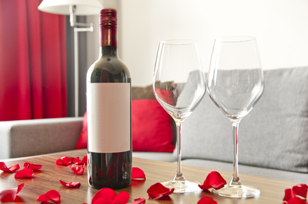 Wine bottle, two glasses and rose petals on a table - romantic afternoon at home
