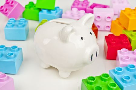 Piggy bank and colorful toy bricks - saving on toys