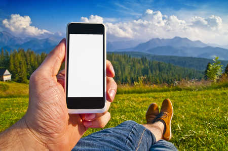 Empty smartphone screen in mans hand against mountain landscape - point of view outdoor technology concept