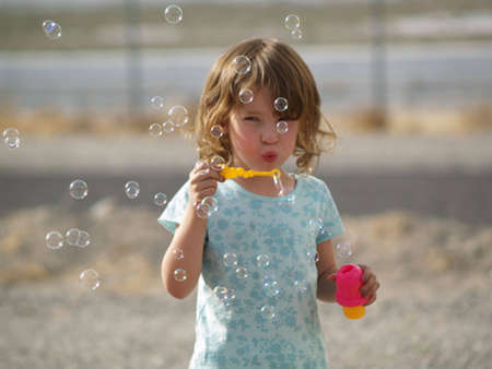 Young girl having fun blowing some bubbles
