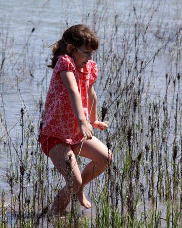 Girl tip toeing through the reeds