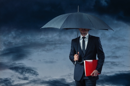 Business man walking through stormy weather holding red wallet photo