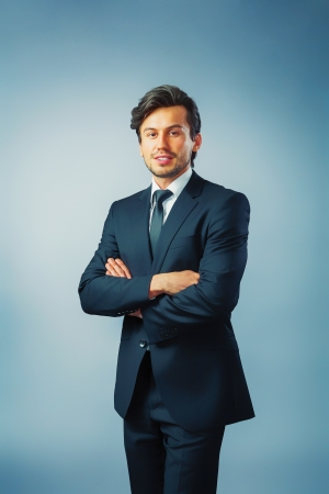 businessman standing in front of blue background