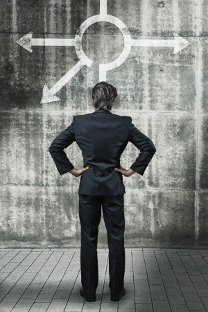 businessman in front of a wall with different direction arrows metaphoric for difficult decisions photo