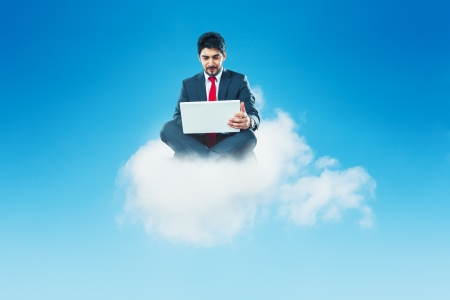 Businessman with laptop on a cloud cloud computing photo