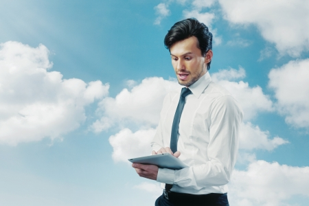 Businessman working with touchpad blue sky photo