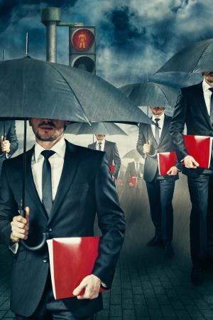 Businessman with umbrella in the rain photo