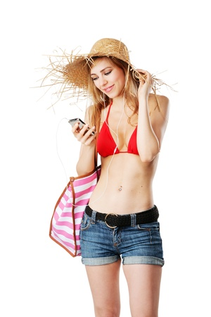 Blonde girl tuning in the right music for the beach isolated on white