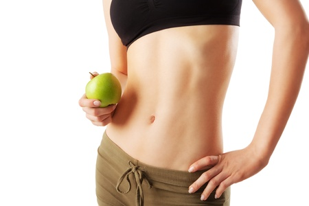 Close up of athletic woman belly holding a green apple in hand isolated on white Stock Photo - 20620500