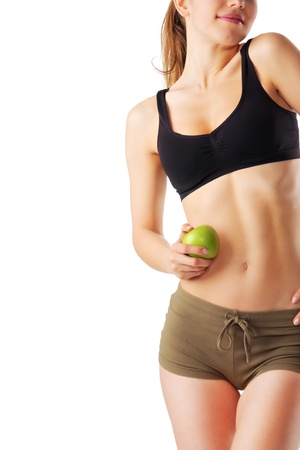 Sporty woman in fitness dress holding green apple isolated on white Stock Photo