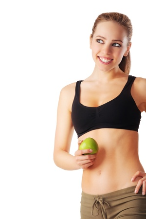 Beautiful young and sporty woman holding green apple and smiling isolated on white Stock Photo - 20620492