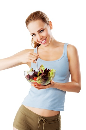 Sporty woman is eating a healthy salad smiling isolated on white
