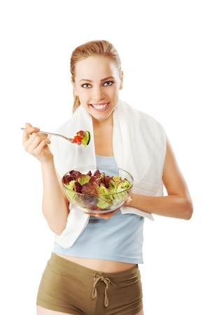 Fit and slim woman with towel  over her shoulder eating a fresh salad isolated on white photo