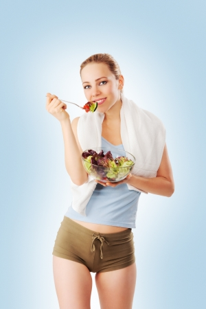 Sporty young woman eating salad blue background photo