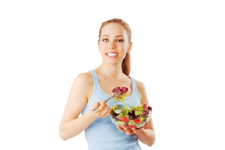 Young woman having a healthy and fresh salad isolated on white