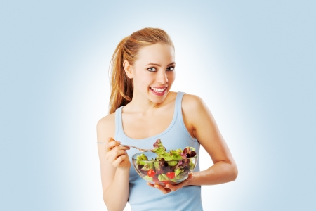 Blonde woman eating salad blue background looking at camera photo