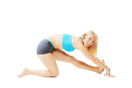 Blonde woman doing gymnastics in a kneeling pose isolated on white Stock Photo - 20953102