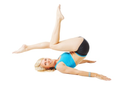 Blonde woman lying on her back doing gymnastics isolated on white Stock Photo - 20953171