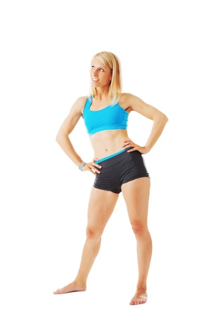 sports wear: Woman in sports wear standing with hands on her hips isolated on white
