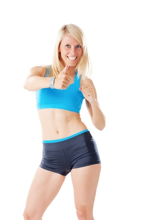 Blonde woman in sports wear showing thumbs up and smiling isolated on white