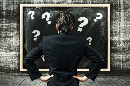 Businessman looking at a billboard with chalk drawn question marks strategy concept photo