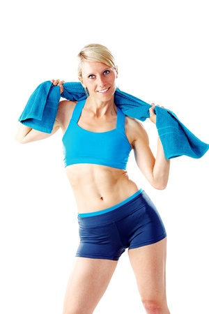 Blonde woman in blue sports wear holding a towel around her shoulder looking to the camera isolated on white