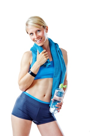 Blonde woman in sports wear smiling to the camera holding a water bottle and blue towel isolated on white Stock Photo - 21602297