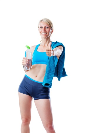 Sporty blonde woman after fitness workout showing thumb up and holding a water bottle isolated on white photo