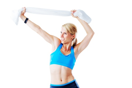 Woman in sport dress enjoying herself holding a white towel isolated on white photo